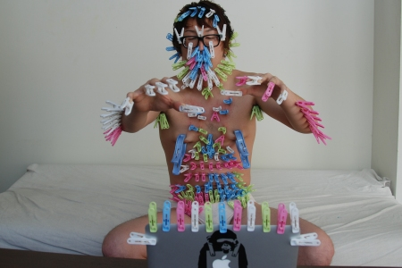 Japanese man covered in clothes pegs