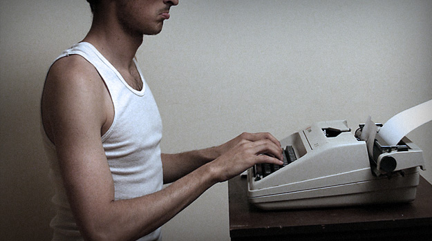 Depressed man using typewriter
